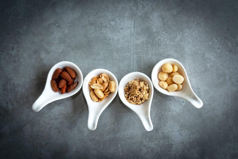 Gesunde Nahrungsmittel Mischnüsse in den weißen Schüsseln mit Nüssen für Diät auf einer konkreten Tabelle Verschiedene Arten von  stockbild
