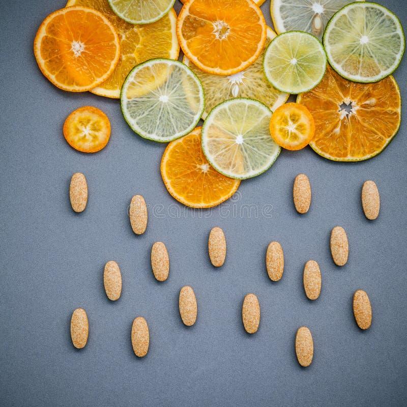 Gesunde Nahrungsmittel und Medizinkonzept Pillen des Vitamins C und des citru stockfoto