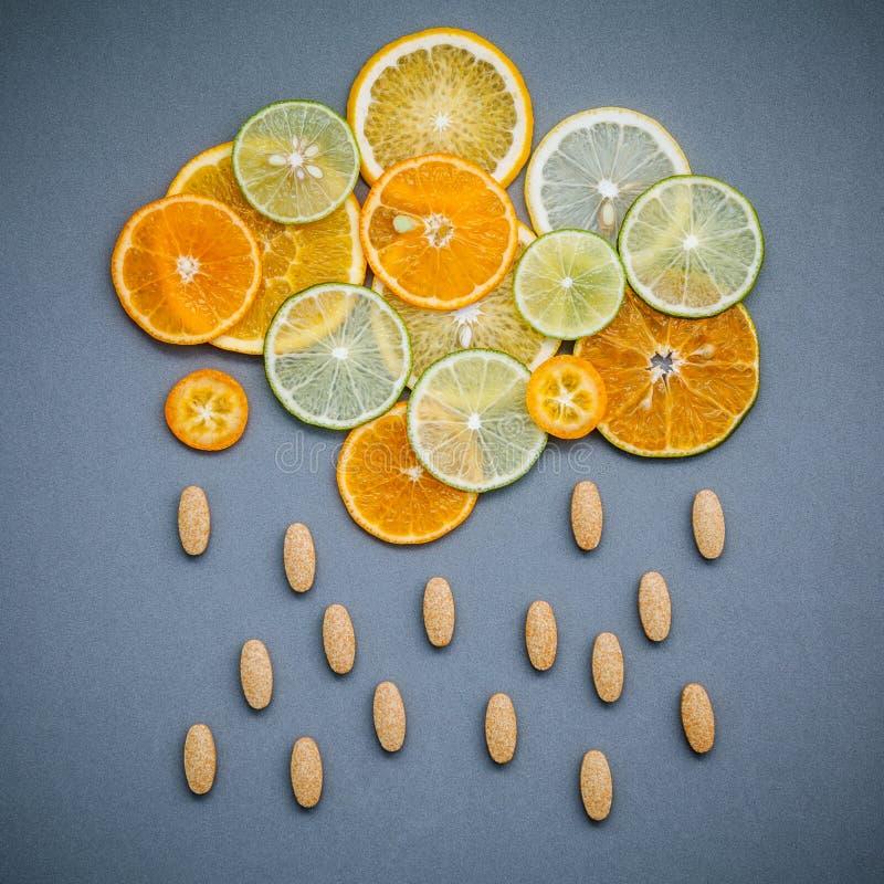 Gesunde Nahrungsmittel und Medizinkonzept Pillen des Vitamins C und des citru stockbild