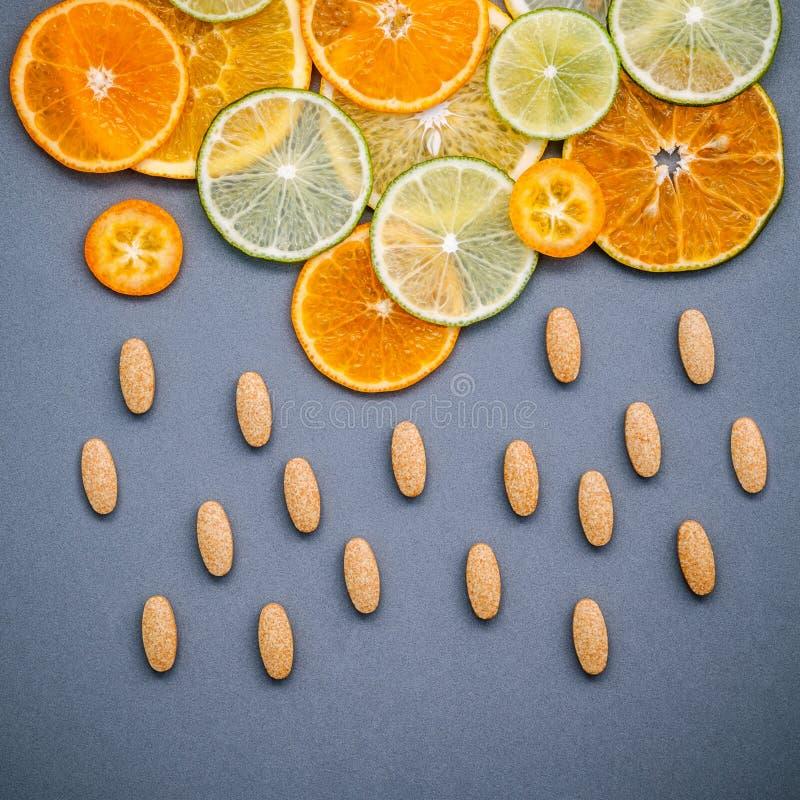 Gesunde Nahrungsmittel und Medizinkonzept Pillen des Vitamins C und des vario stockbild