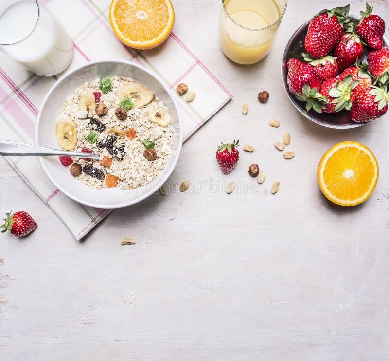 Gesunde Nahrungsmittel, vegetarische Konzepthaselnüsse, Erdbeeren und Orangen, Hafermehl, Milchsaftgrenze, Platz für Text auf höl stockfotos