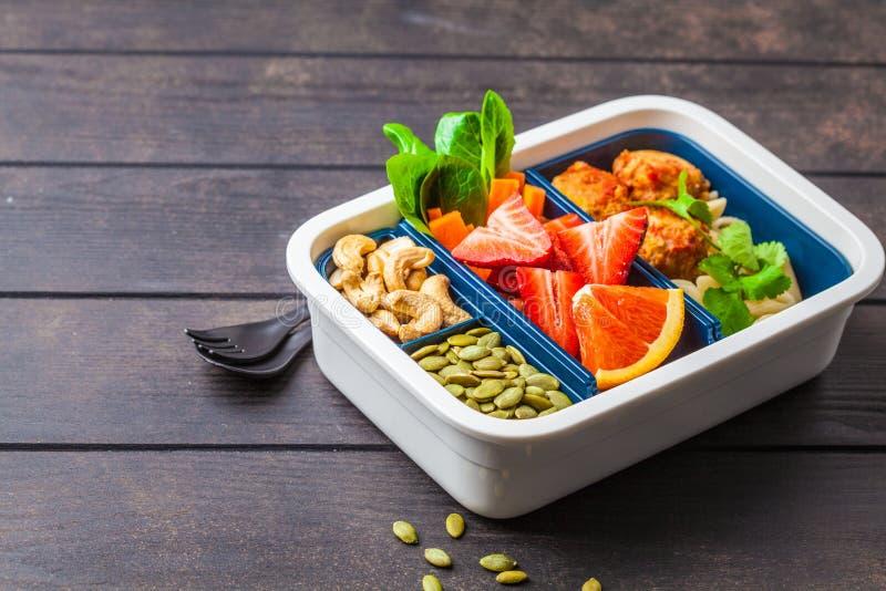 Gesunde Nahrungsmittelbrotdose Nahrung des strengen Vegetariers: Bohnenfleischklöschen, -teigwaren, -gemüse, -beeren, -samen und  stockbild