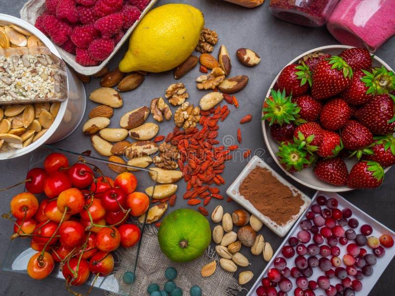 Gesunde Nahrungsmittelsaubere Essenauswahl: Samen-, superfoods-, Gemüse- und Fruchtpulver auf grauem konkretem Hintergrund lizenzfreies stockfoto
