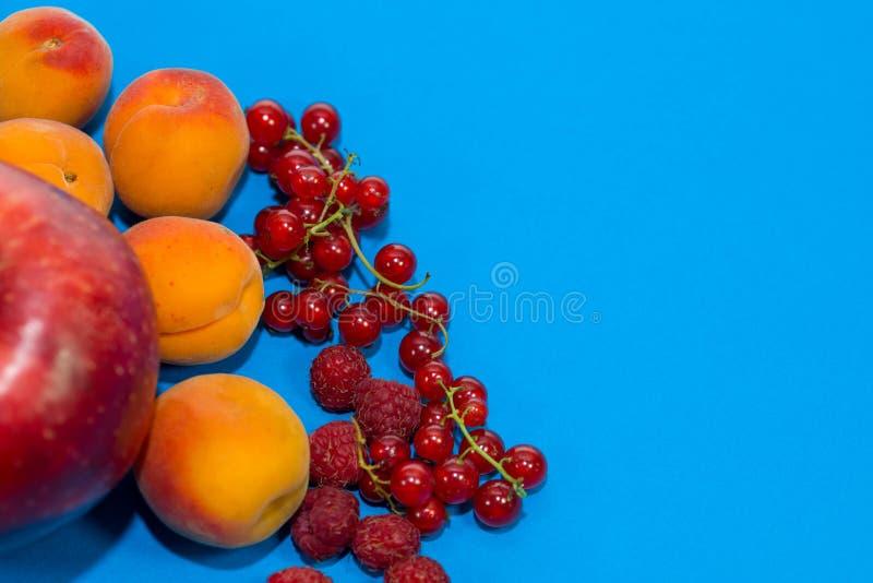 Gesunde Nahrungszusammensetzung, Himbeeren, Aprikosen, Apfel und rote Johannisbeeren auf blauem Hintergrund stockfotos