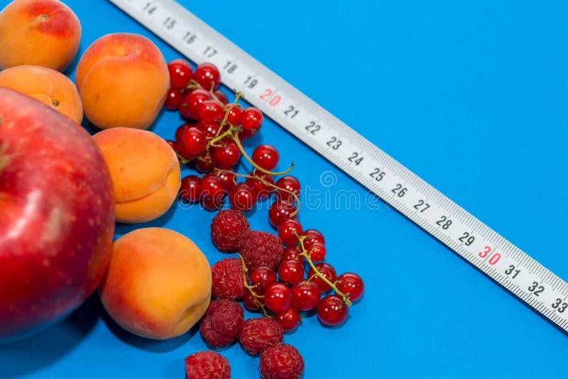 Gesunde Nahrungszusammensetzung, Maßband, Himbeeren, Aprikosen, Apfel und rote Johannisbeeren stockbilder