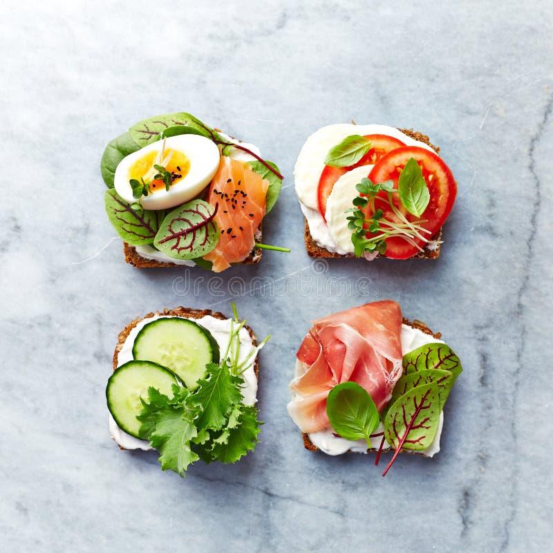 Gesunde offene Sandwiche mit Gemüse, Lachsen, Schinken, Kräutern und Weichkäse stockfotos