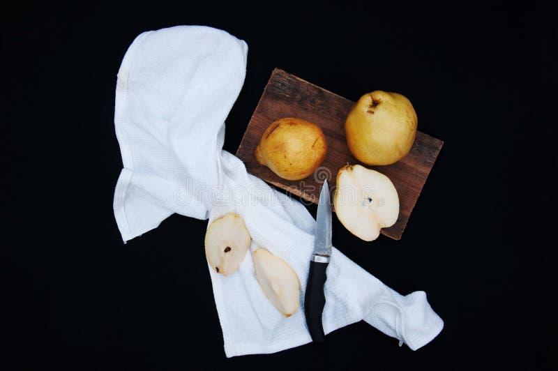 Gesunde organische gelbe Birnen auf dem Schreibtisch Ein Ananasschnitt geschnitten zur Hälfte Reife frische organische Birnen auf lizenzfreie stockfotos