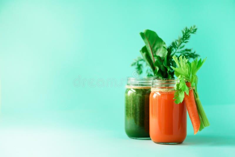 Gesunde organische grüne und orange Smoothies auf blauem Hintergrund Detox trinkt im Glasgefäß vom Gemüse - Karotte lizenzfreies stockbild