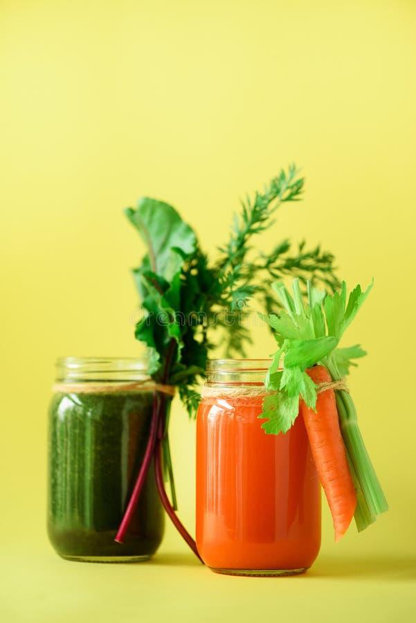 Gesunde organische grüne und orange Smoothies auf gelbem Hintergrund Detox trinkt im Glasgefäß vom Gemüse - Karotte lizenzfreie stockfotografie