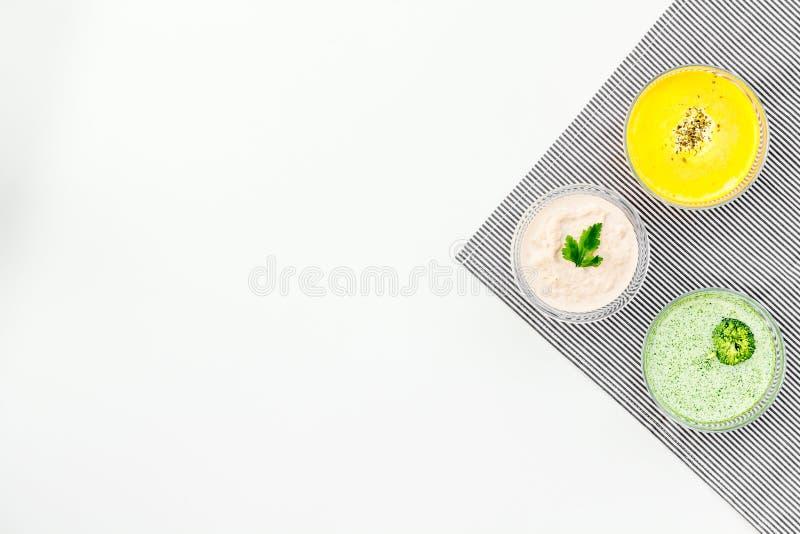 Gesunde organische vegetarische Mahlzeit Sahnesuppenkonzept Farbige Suppen mit Kürbis, Brokkoli, Pilze auf weißem Hintergrund lizenzfreie stockfotos