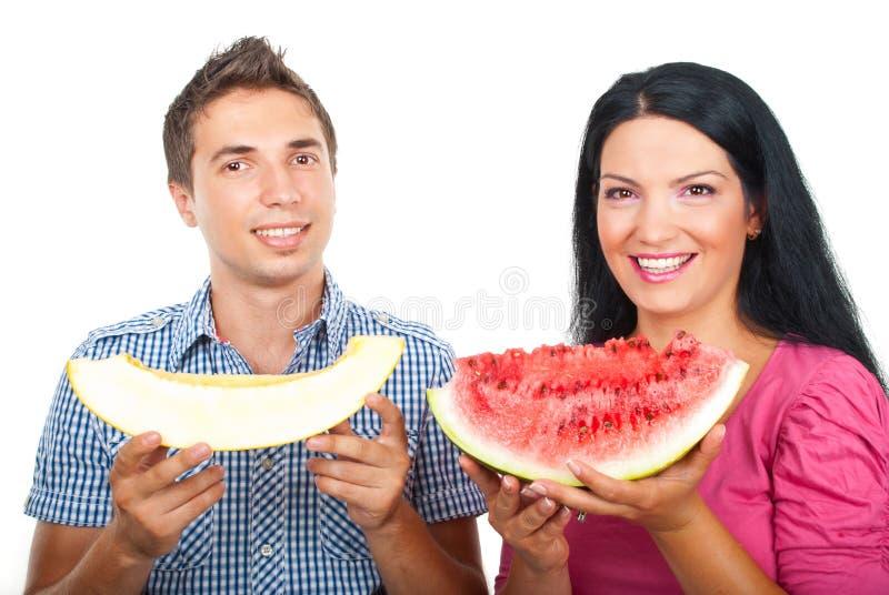 Gesunde Paare mit Wassermelone und Melone stockfotos