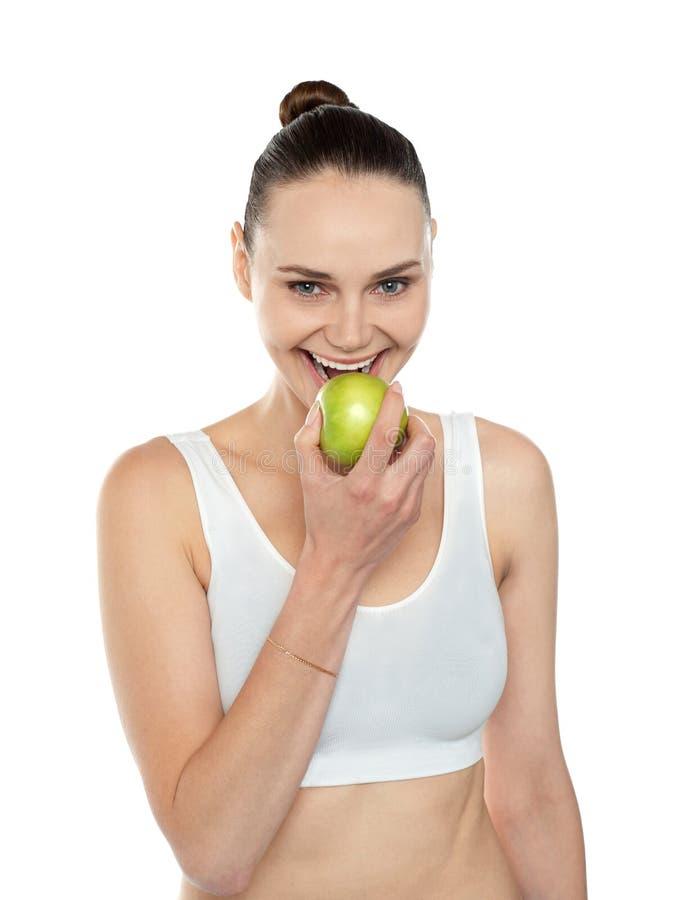 Gesunde Pass-Sitzfrau, die frischen grünen Apfel isst stockfotografie