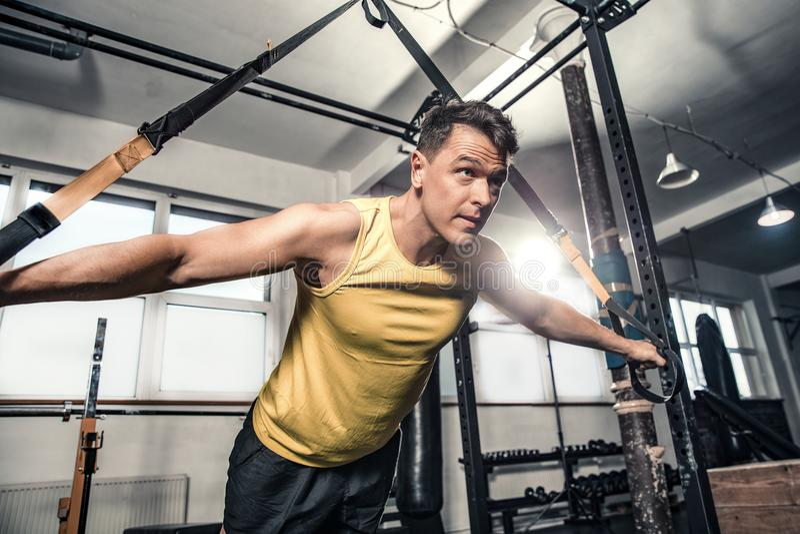 Gesunde Praxis des jungen Mannes auf gymnastischen Bändern lizenzfreie stockfotos