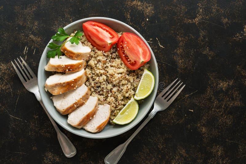 Gesunde Quinoanahrung mit Hühnerleiste und -tomaten auf Schmutzbraunhintergrund Draufsicht, Kopienraum Gesundes Essenkonzept lizenzfreies stockbild