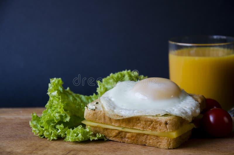 Gesunde Sandwiche mit Käse und leicht Spiegelei stellten sich auf einem hölzernen Brett mit Salat, Tomate und Orangensaft dar stockfoto