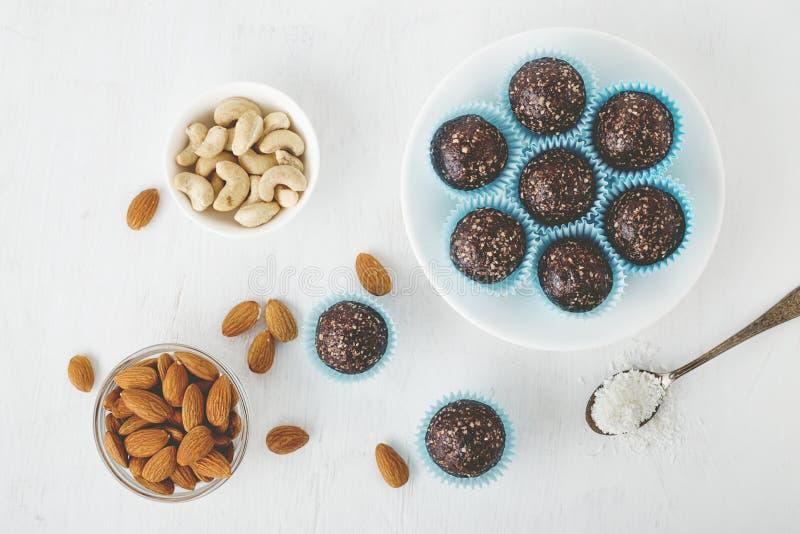 Gesunde Schokoladenenergie beißt mit Nüssen, Daten, Kakaopulver, Kokosnussflocken auf weißer Tabelle stockbild