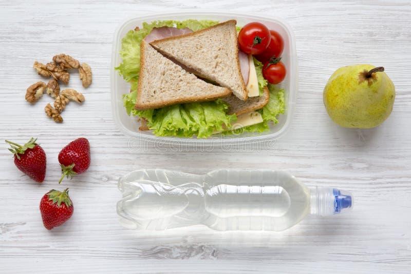 Gesunde Schulbrotdose mit frischen organischen Gemüsesandwichen, -walnüssen, -flasche Wasser und -früchten auf weißem hölzernem H lizenzfreie stockfotos