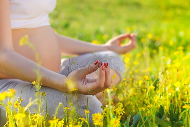 Gesunde schwangere Frau, die draußen Yoga in der Natur tut lizenzfreie stockfotos