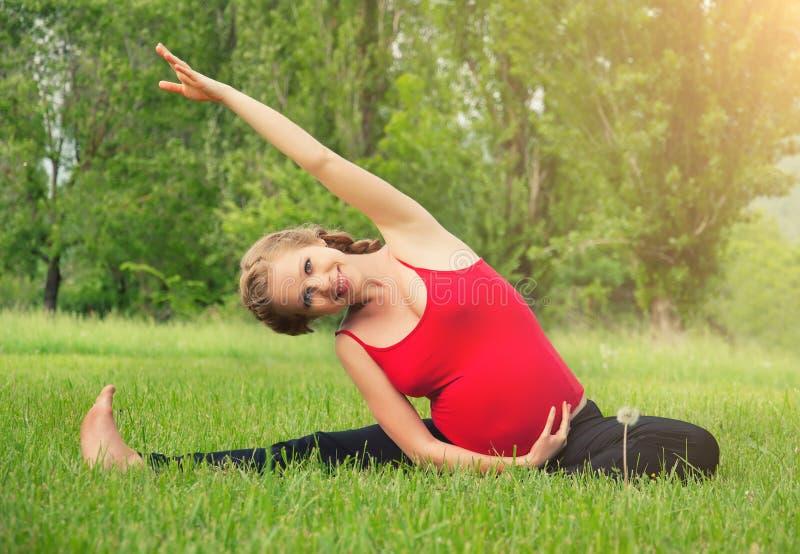 Gesunde schwangere Frau, die Yoga in der Natur tut stockbild