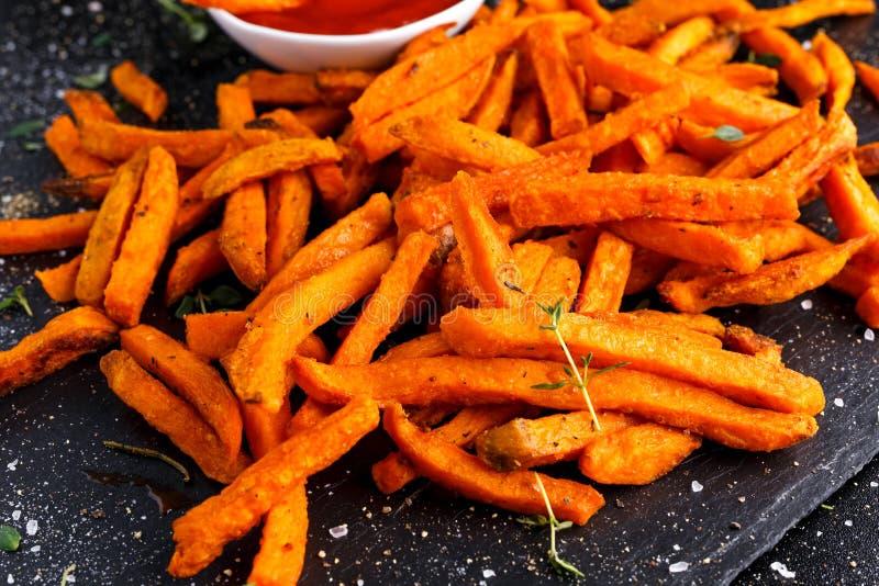 Gesunde selbst gemachte gebackene orange Süßkartoffel brät mit Ketschup, Kräutern, Salz und Pfeffer stockfotos