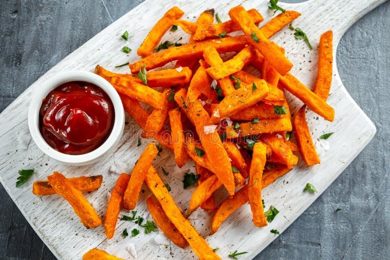 Gesunde selbst gemachte gebackene orange Süßkartoffel brät mit Ketschup, Salz, Pfeffer auf weißem hölzernem Brett lizenzfreies stockfoto