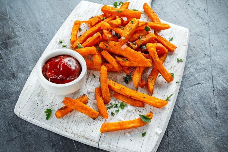 Gesunde selbst gemachte gebackene orange Süßkartoffel brät mit Ketschup, Salz, Pfeffer auf weißem hölzernem Brett stockfotografie