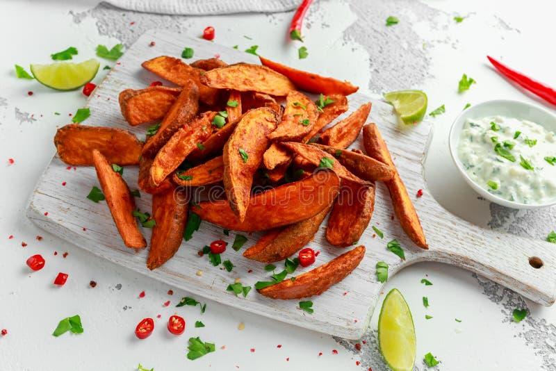 Gesunde selbst gemachte gebackene orange Süßkartoffelkeile mit neuem Sahnebad sauce, Kräuter, Salz und Pfeffer lizenzfreies stockfoto