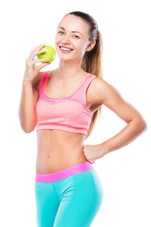 Gesunde und geeignete Frau, die einen grünen Apfel lokalisiert über Weiß isst lizenzfreie stockbilder