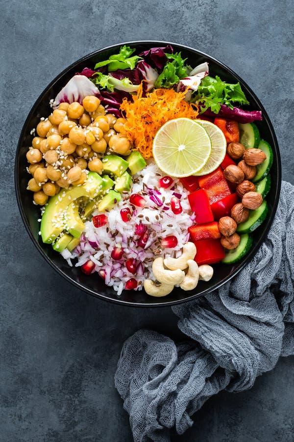 Gesunde Vegetarier Buddha-Schüssel mit Frischgemüsesalat, Reis, Kichererbse, Avocado, Gemüsepaprika, Gurke, Karotte, Granatapfel lizenzfreie stockfotos