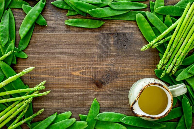 Gesunde vegetarische Nahrung Spargel und Erbse auf dunklem hölzernem copyspace Draufsicht des Hintergrundes stockfotografie