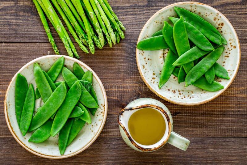 Gesunde vegetarische Nahrung Spargel und Erbse nahe einem Krug Öl auf Draufsicht des dunklen hölzernen Hintergrundes stockfoto