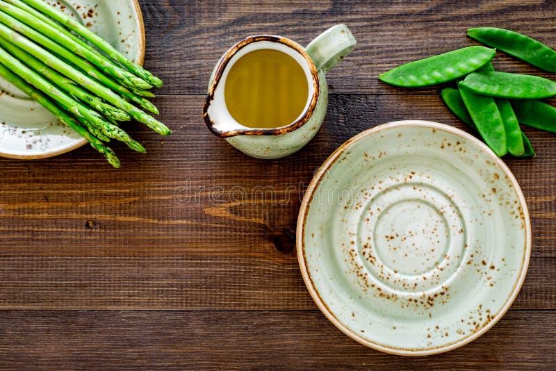 Gesunde vegetarische Nahrung Spargel und Erbse nahe einem Krug Öl auf dunklem hölzernem copyspace Draufsicht des Hintergrundes lizenzfreies stockfoto