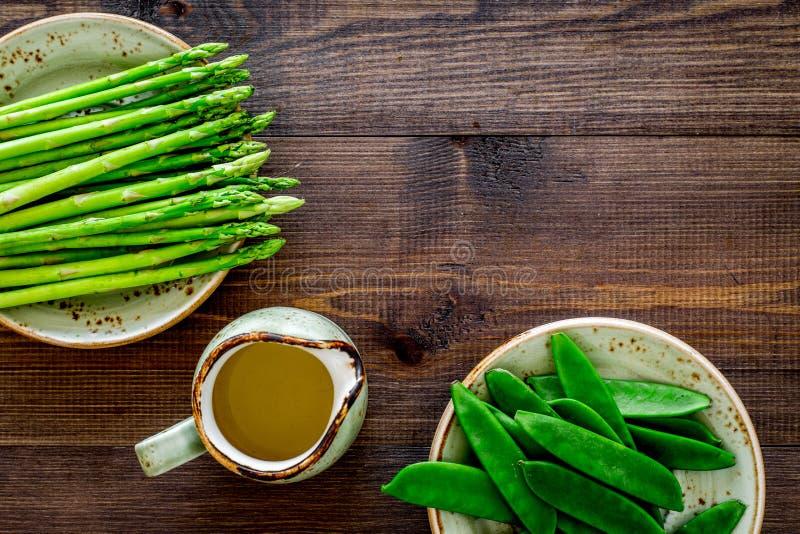 Gesunde vegetarische Nahrung Spargel und Erbse nahe einem Krug Öl auf dunklem hölzernem copyspace Draufsicht des Hintergrundes lizenzfreie stockfotografie