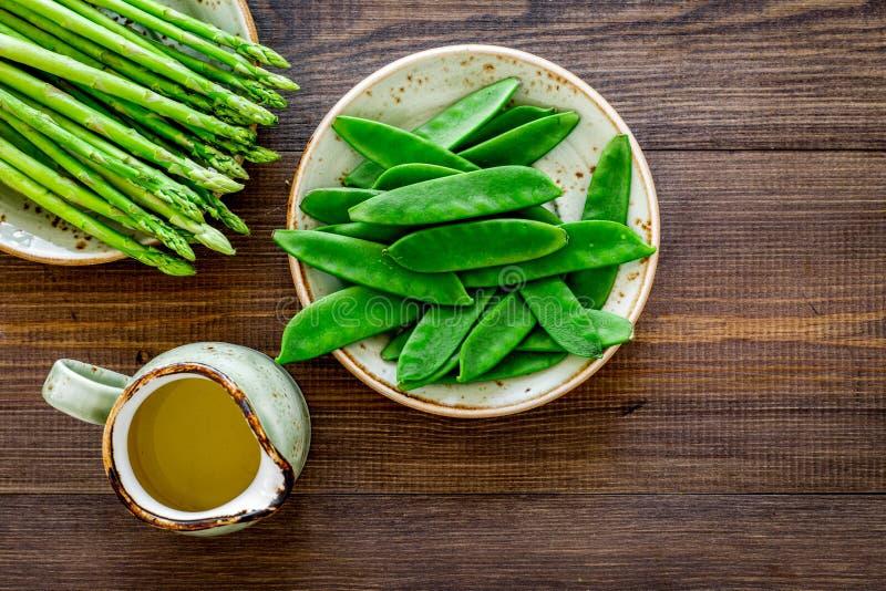 Gesunde vegetarische Nahrung Spargel und Erbse nahe einem Krug Öl auf dunklem hölzernem copyspace Draufsicht des Hintergrundes stockfotos