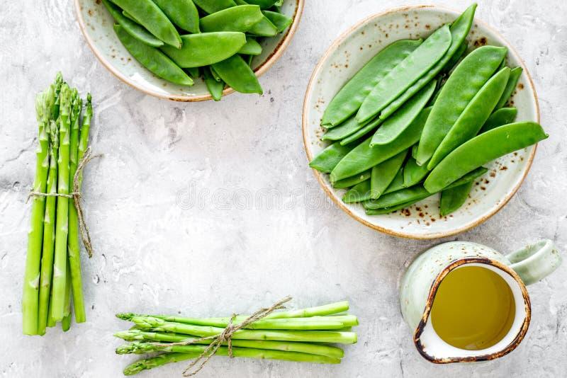 Gesunde vegetarische Nahrung Spargel und Erbse nahe einem Krug Öl auf grauem Steincopyspace Draufsicht des hintergrundes lizenzfreies stockfoto