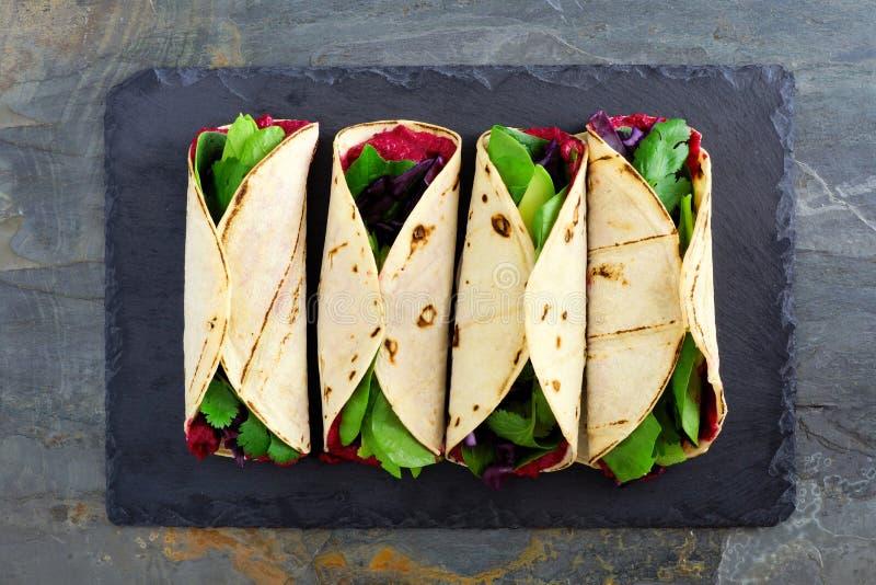 Gesunde Verpackungen mit hummus, Avocado und Spinat der roten Rübe, über Ansicht über Schiefer stockfoto