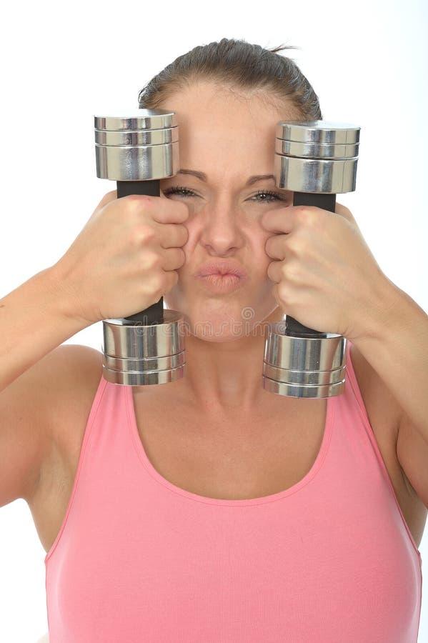 Gesunde verrückte junge Frau, die stumme Bell-Gewichte hält und dummen Gesichtsausdruck zieht lizenzfreie stockfotografie