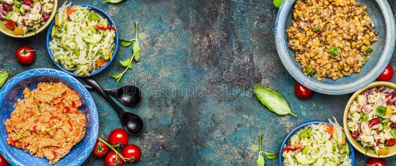 Gesunde verschiedene Salatschüsseln auf dunklem Weinlesehintergrund Landsalate in den rustikalen Schüsseln Salatbar, Draufsicht,  stockbild