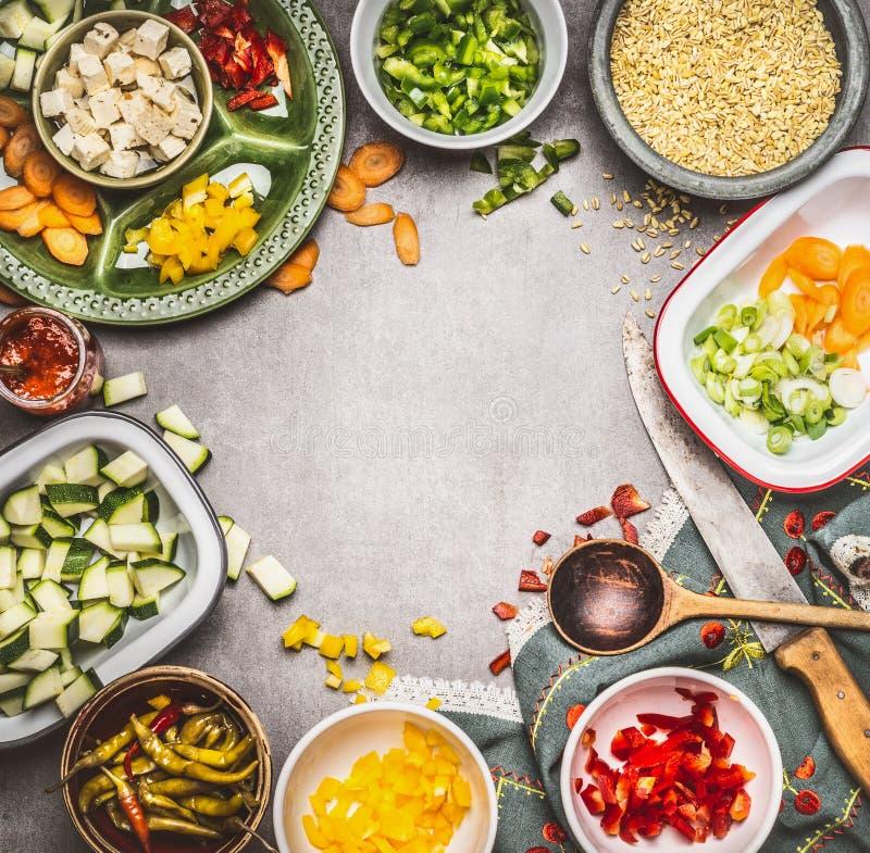 Gesunde Vorbereitung des vegetarischen Tellers mit gewürfeltem Feta, geschnittenem Gemüse in den Schüsseln, Perlgerste, Löffel un lizenzfreies stockfoto