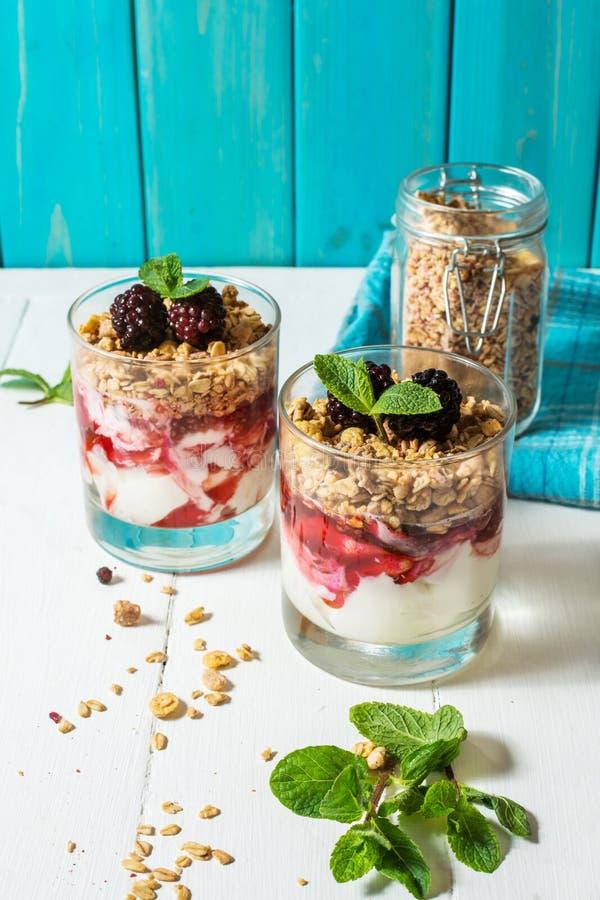 Gesunder überlagerter Nachtisch mit Jogurt, Granola, Stau, Brombeere im Glas auf hölzernem Hintergrund lizenzfreie stockfotografie