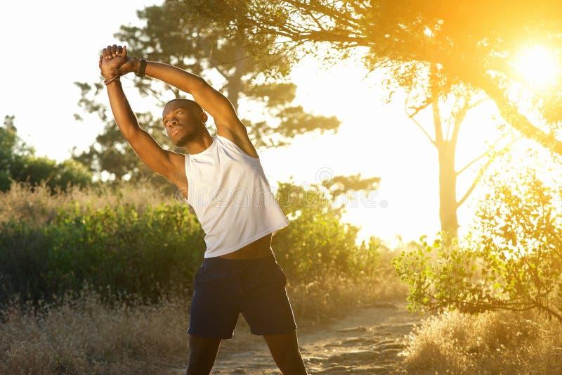 Gesunder Afroamerikanermann, der draußen Muskeln ausdehnt stockfotografie