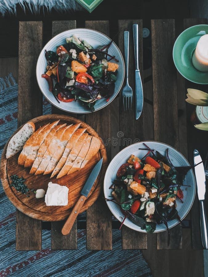 Gesunder bunter Salat des strengen Vegetariers und selbst gemachtes Brot auf einem Weinleseholztisch mit Blumen stockbilder