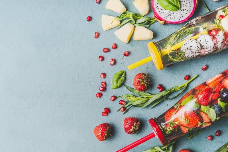 Gesunder Detox goss Wasser mit Früchten, die Beeren hinein, die mit frischen Kräutern in den Flaschen mit Trinkhalm auf grauem Hi stockfotos