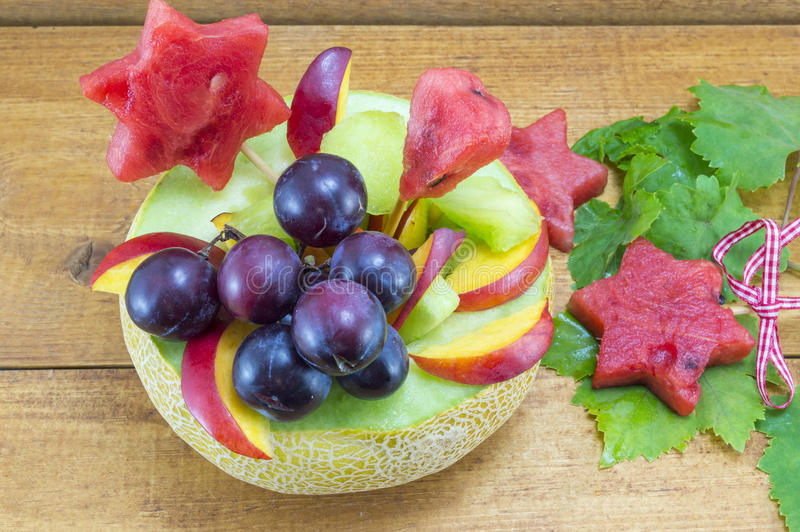 Gesunder einzigartiger Obstsalat diente in einer frischen Melone auf einem hölzernen t lizenzfreie stockfotos