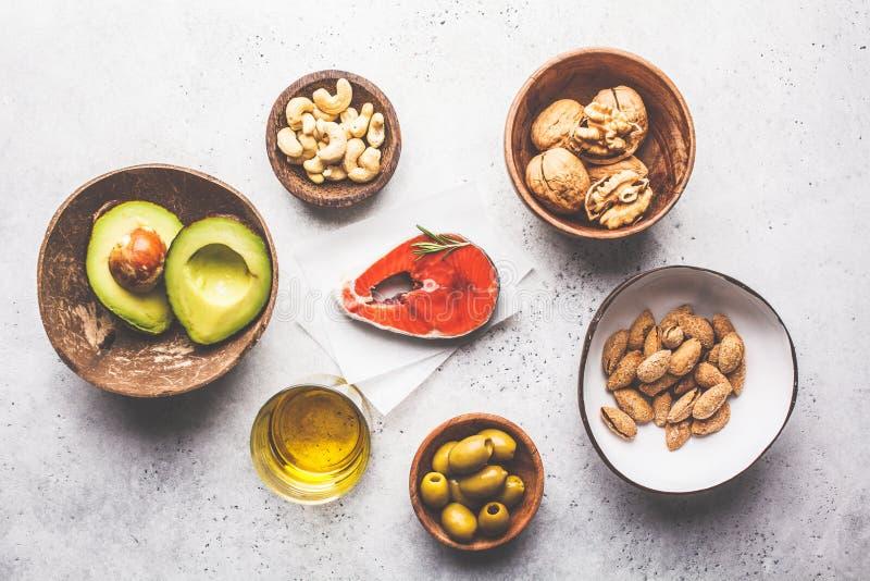 Gesunder fetter Nahrungsmittelhintergrund Fische, Nüsse, Öl, Oliven, Avocado auf weißem Hintergrund, Draufsicht stockbilder