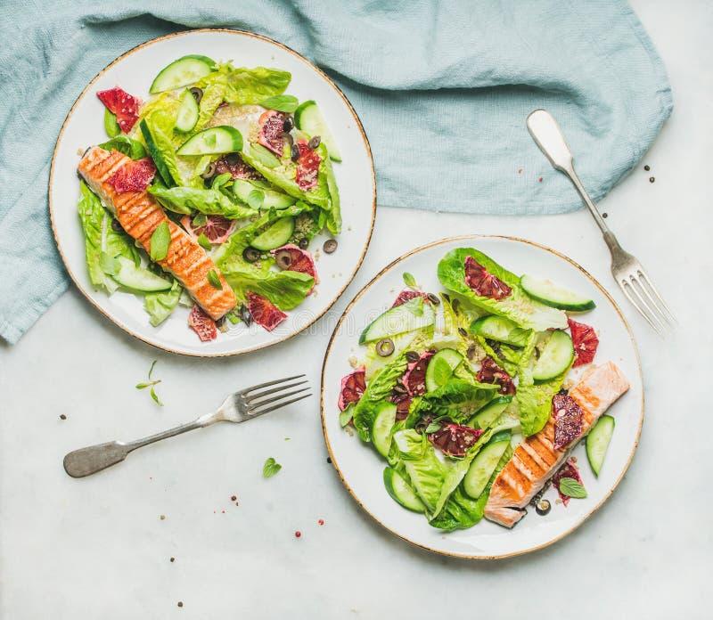 Gesunder Frühlingssalat mit gegrillten Lachsen, Orange, Oliven und Quinoa lizenzfreies stockbild
