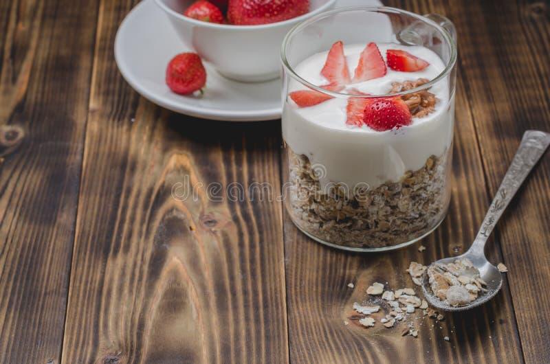 Gesunder Frühstück Jogurt, frische Erdbeere, Löffel mit dem zerstreuten Körnchen auf einem Holztisch Copyspace lizenzfreies stockfoto