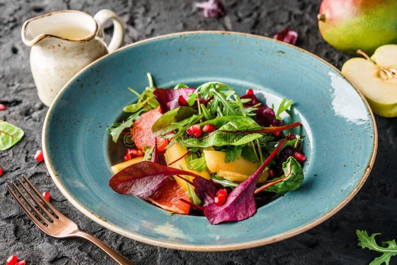 Gesunder frischer Obstsalat mit Grüns und Soße in der Schüssel über dunklem Hintergrund Gesunde Nahrung, oben nährender Vegetarie stockfotos