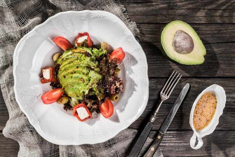 Gesunder frischer Salat mit Avocado, Grüns, Arugula, Kirschtomaten, Oliven und Käse in der Platte über rustikalem Holztisch stockfotos