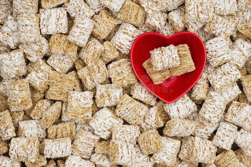 Gesunder ganzer Korngetreidehintergrund mit einer Herzschüssel stockfoto